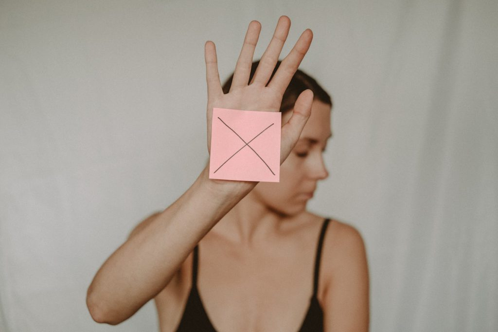 woman with paper with cross sign
